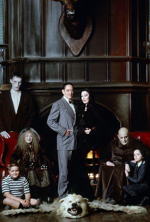 Fester (Christopher Lloyd, 2.v.l.) taucht bei der Familie Addams auf und behauptet, der seit Jahren verschollene Bruder von Gomez Addams (Raul Julia... - Bildquelle: Paramount Pictures Global
