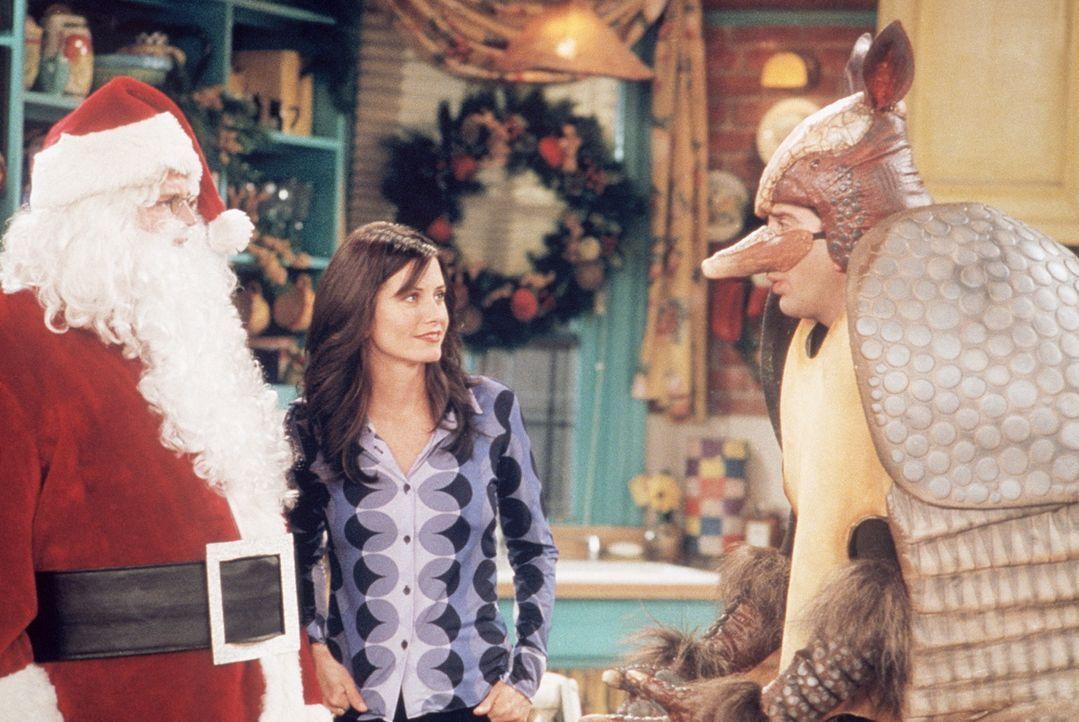 Monica (Courteney Cox, M.) beobachtet den Konkurrenzkampf zwischen dem Weihnachtsmann (Matthew Perry, l.) und dem Gürteltier (David Schwimmer, r.). - Bildquelle: TM+  2000 WARNER BROS.