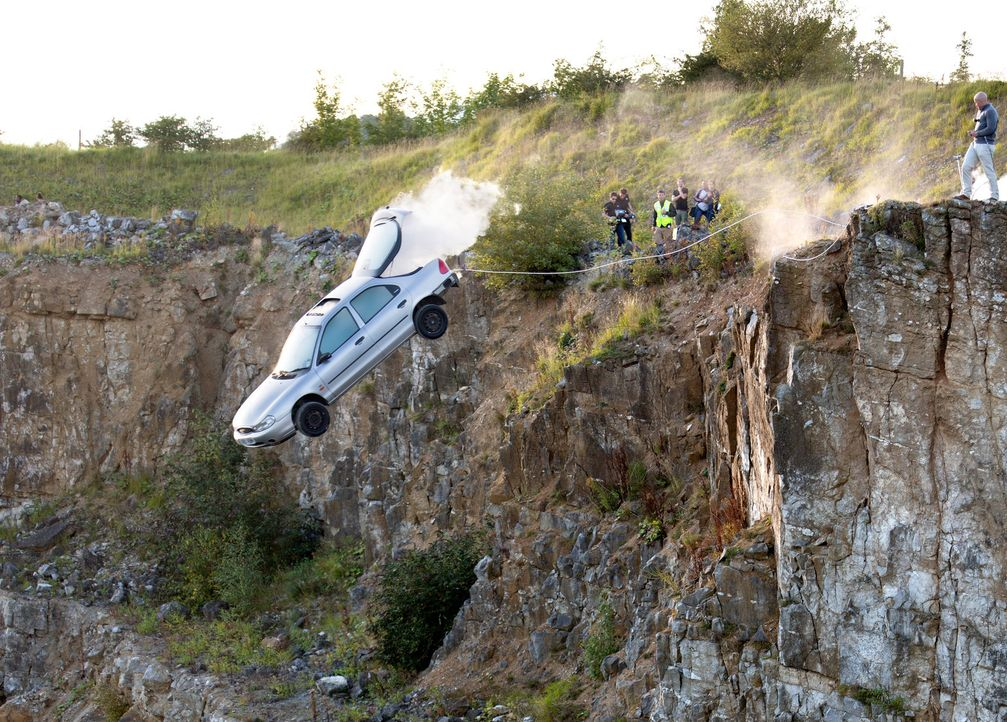 Jonathan Goodwin muss, an einem Wagen mit Raketenantrieb hängend, ein Schloss öffnen, um nicht eine 60 Meter hohe Klippe hinunter zu stürzen ... - Bildquelle: Objective Productions/UKTV