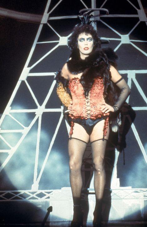 Der Hausherr Dr. Frank N. Furter (Tim Curry) tritt, gekleidet in Mieder, Strapse und hochhackigen Schuhen, auf die Bühne … - Bildquelle: 1975 Houtsnede Maatschappi N.V.