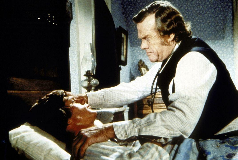Doktor Baker (Kevin Hagen, r.) behandelt Almanzo Wilder (Dean Butler, l.), der an Diphterie erkrankt ist. - Bildquelle: Worldvision