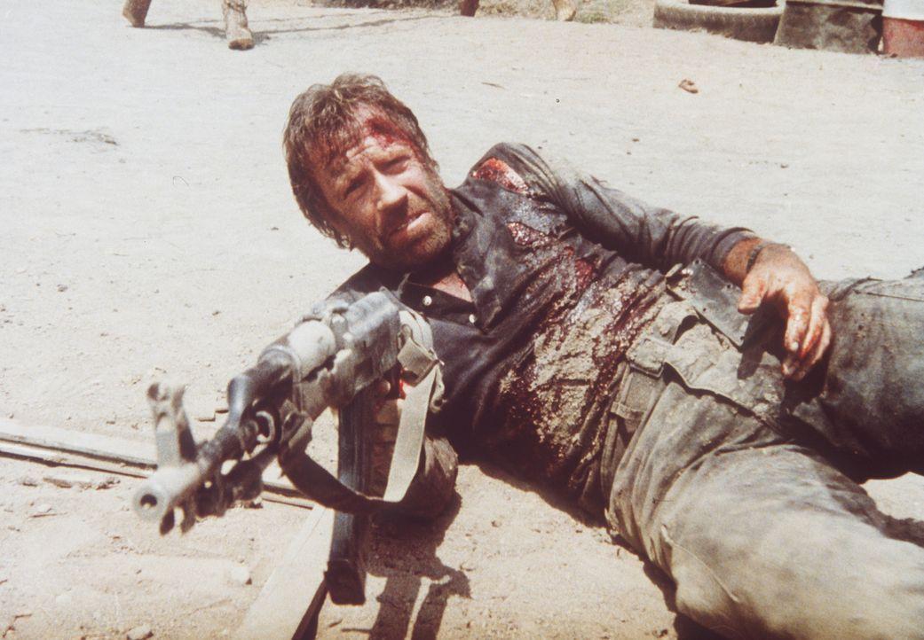 Auch schwer verletzt und mit den Kräften am Ende, gibt Braddock (Chuck Norris) nicht auf und schießt sich den Weg frei ... - Bildquelle: Cannon Films
