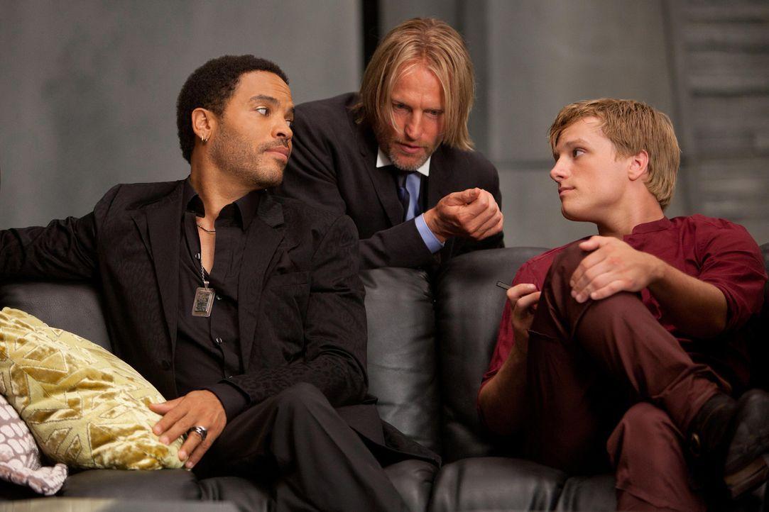 Als Cinna (Lenny Kravitz, l.) und Haymitch Abernathy (Woody Harrelson, M.) erfahren, dass Peeta (Josh Hutcherson, r.) seit vielen Jahren in Katniss... - Bildquelle: Studiocanal GmbH