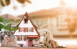 Euromünzen neben Haus symbolisieren das Investment in Immobilien