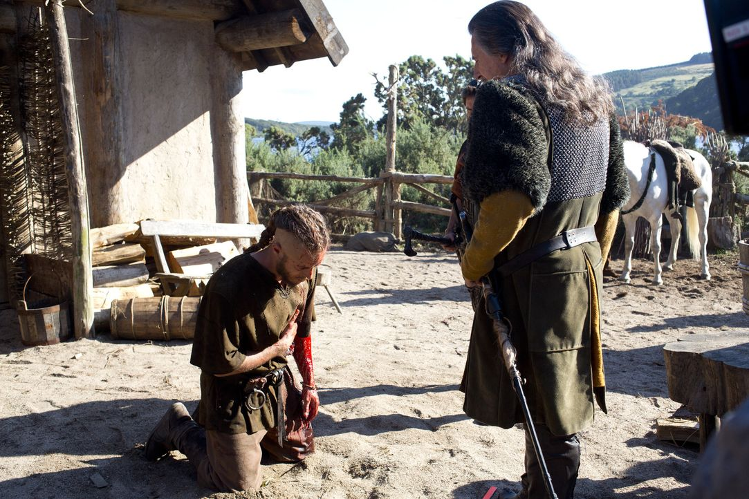 Schwer verletzt ergibt sich Ragnar (Travis Fimmel, l.) seinem Stammesfürsten Earl Haraldson (Gabriel Byrne, r.). Dieser verurteilt ihn sofort zum To... - Bildquelle: 2013 TM TELEVISION PRODUCTIONS LIMITED/T5 VIKINGS PRODUCTIONS INC. ALL RIGHTS RESERVED.