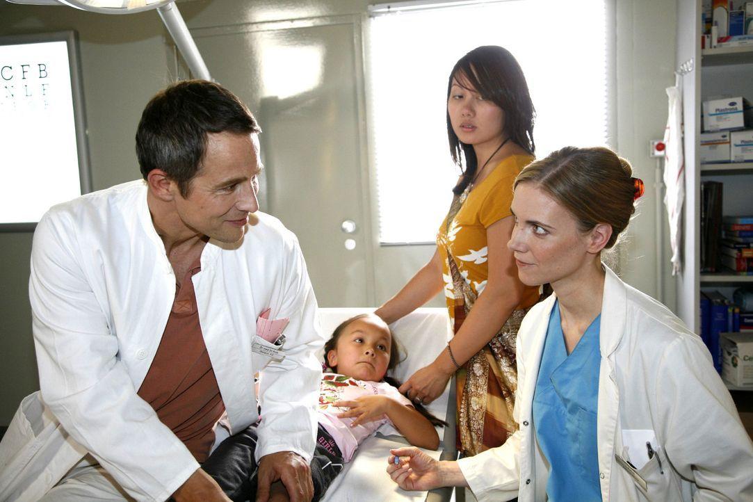 Luisa (Jana Voosen, r.) und Stephan (Andreas Brucker, l.) untersuchen die kleine Joy (Joelle Nguyen, M.), die mit ihrem Kindermädchen Suree (Chi La... - Bildquelle: Mosch Sat.1