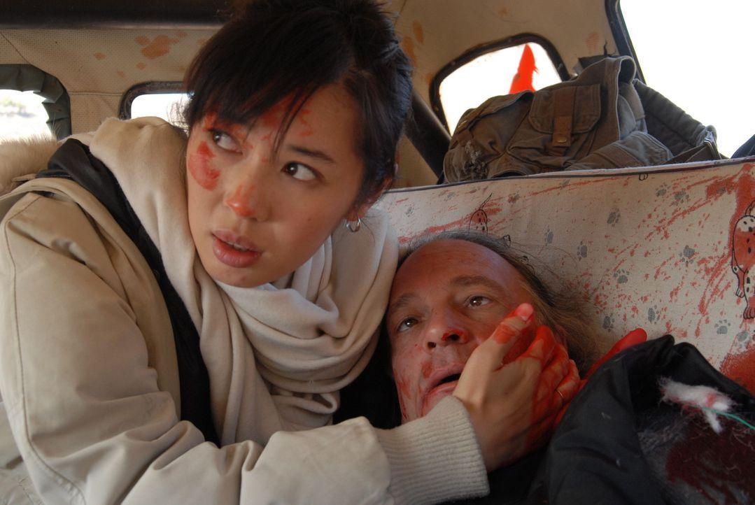 Verzweifelt versucht Anika (Nan Yu, l.), Chambers (William Shriver, r.) dem Tod noch zu entreißen. Doch ihr Stiefvater erliegt seinen schweren Verl...