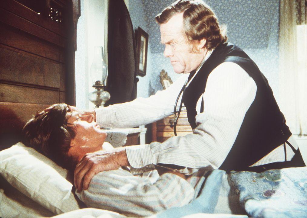 Dr. Baker (Kevin Hagen, r.) behandelt Almanzo Wilder (Dean Butler, l.), der an Diphterie erkrankt ist. - Bildquelle: Worldvision