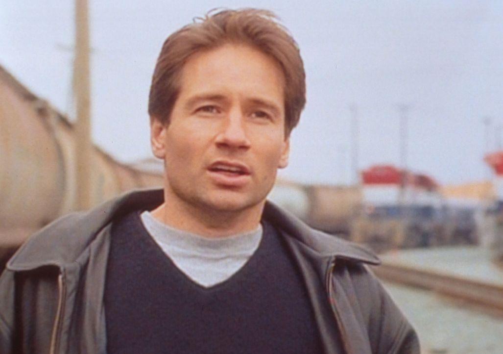 Mulder (David Duchovny) beobachtet auf einem Bahnhof, dass mehrere Japaner ein Wesen, dass einem Außerirdischen ähnelt, in einen regierungseigenen E... - Bildquelle: TM +   2000 Twentieth Century Fox Film Corporation. All Rights Reserved.