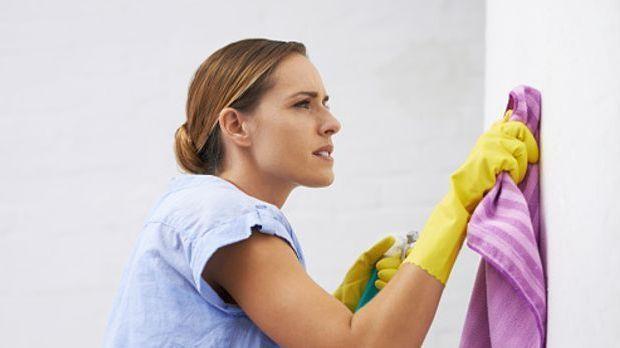 Junge Frau putzt energisch mit einem Lappen die Wand
