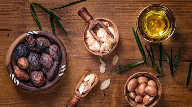 Arganöl und Früchte in unterschiedlichen Reifegraden liegen auf einem Tisch