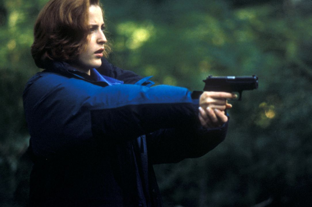 Scully (Gillian Anderson) zielt auf einen unsichtbaren Gegner, den sie zunächst für ein Raubtier hielt. - Bildquelle: TM +   2000 Twentieth Century Fox Film Corporation. All Rights Reserved.