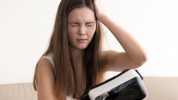 junge Frau hält sich vor Schwindel den Kopf nachdem sie eine VR-Brille getrag...