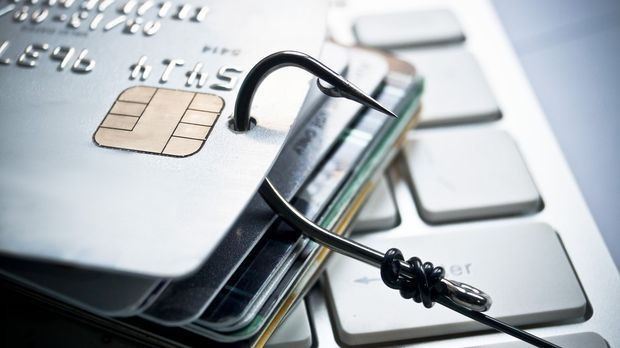 Angelhaken zieht an Kreditkarten, die auf Laptop liegen