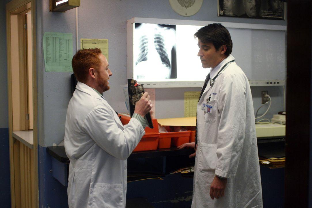 Morris (Scott Grimes, l.) überrascht Luka (Goran Visnjic, r.) mit einem Las Vegas - Reiseprospekt und versucht ihm schmackhaft zu machen, wie toll... - Bildquelle: Warner Bros. Television