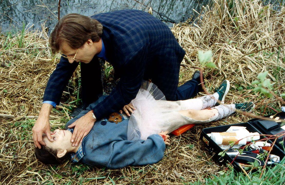 Dr. Gregor Lüders (Ralf Lindermann, oben) leistet der kleinen Lisa (Jill Böttcher, unten) erste Hilfe am Unfallort. - Bildquelle: Daehn Sat.1