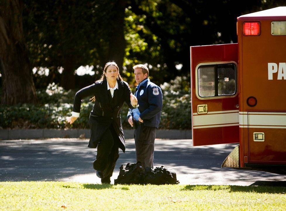 Von einem Sanitäter (John Donahue, r.) erfährt Delia (Camryn Manheim, l.), dass von der Villa aus, die sie verkaufen soll, ein Notruf gesendet wurde... - Bildquelle: ABC Studios