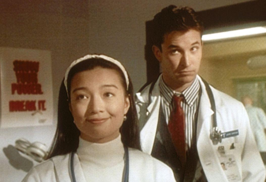 John Carter (Noah Wyle, r.) hört missmutig, wie Deb (Ming-Na Wen, l.) für ihren mutigen Einsatz von Dr. Benton gelobt wird. - Bildquelle: TM+  WARNER BROS.