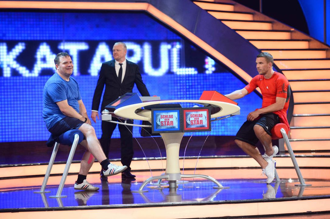 Stefan Raab (M.) ist gespannt, wer das Spiel gewinnen wird - Lukas Podolski (r.) oder Elton (l.)? - Bildquelle: Willi Weber ProSieben