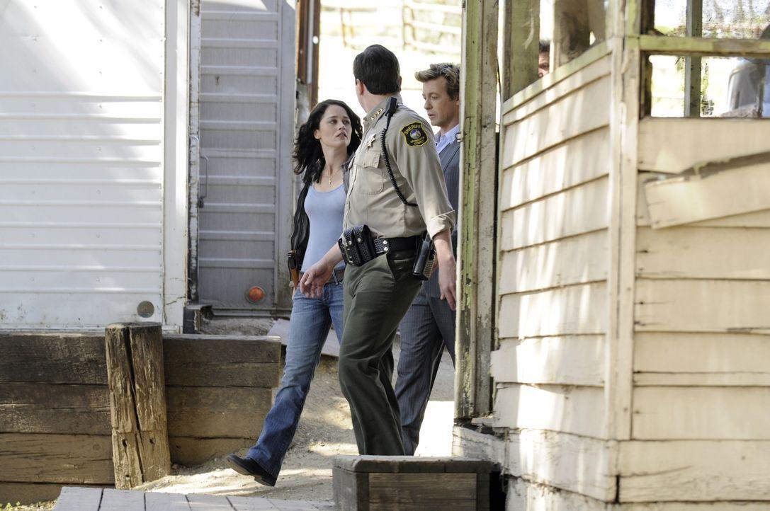 Als die Leiche der jungen Emma Plaskett auf einem Staatsgrundstück gefunden wird, werden Teresa (Robin Tunney, l.), Patrick (Simon Baker, r.) und da... - Bildquelle: Warner Bros. Television