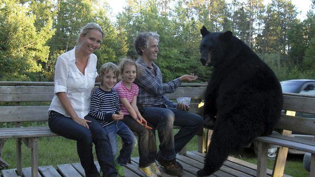 Gordon Buchanan (r.) stellt seiner Familie einen großen männlichen Schwarzbär...
