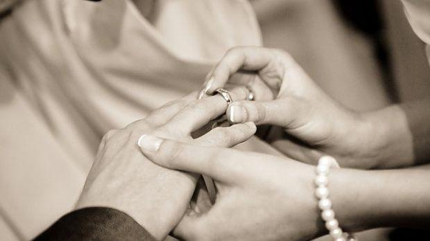 Ehering wird an den Finger gesteckt