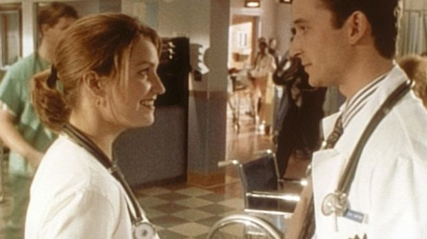 Carter (Noah Wyle, r.) erweist Dr. Lewis (Sherry Stringfield, l.) einen Diens...