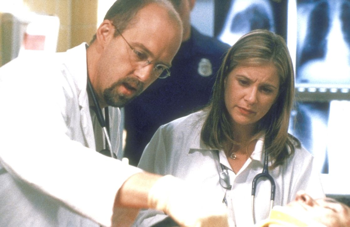 Greene (Anthony Edwards, l.) weist die Praktikantin Lucy (Kellie Martin, r.) in die Untersuchung eines Komapatienten ein. - Bildquelle: TM+  2000 WARNER BROS.