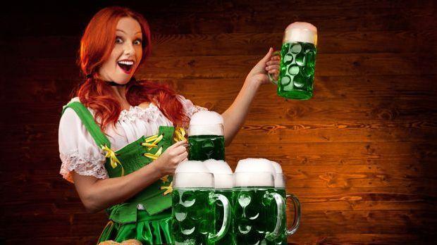Rothaarige irische Frau hält Bierkrüge mit grünem Bier