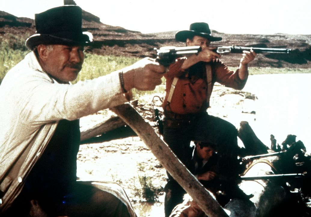 Sam Clayton (Ward Bond, l.) und Ethan (John Wayne, r.) verteidigen sich gegen angreifende Indianer. - Bildquelle: Warner Bros.