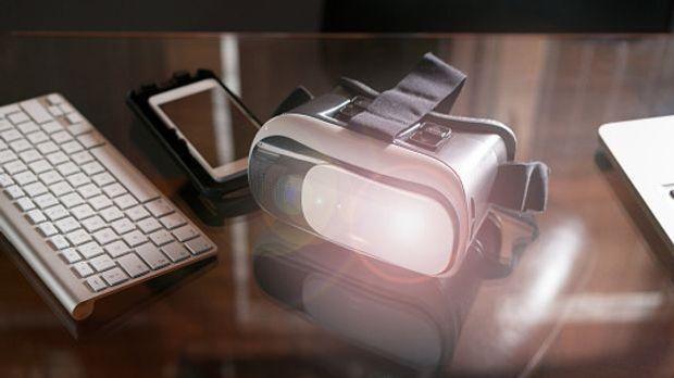 VR-Brille liegt neben Smartphone und Tastatur auf einem Tisch