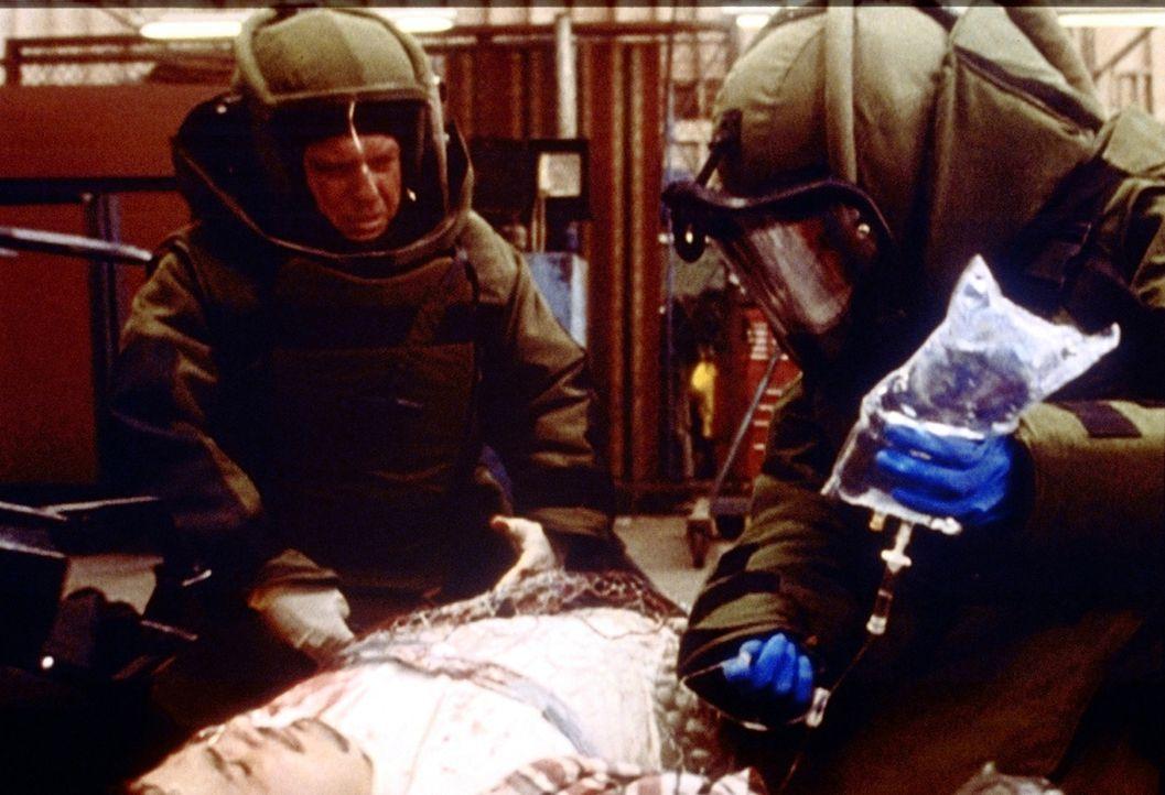 Im Schutzanzug behandelt Greene (Anthony Edwards, r.) einen verletzten Geiselnehmer, der mehrere Ladfungen Dynamit am Körper trägt. - Bildquelle: TM+  2000 WARNER BROS.