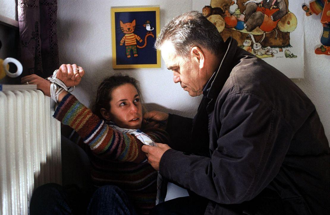 Wolff (Jürgen Heinrich, r.) befreit das angekettete Kindermädchen (Nele Jonca, l.), das bei der Entführung des kleinen Markus überwältigt wurde. - Bildquelle: Leslie Haslam Sat.1