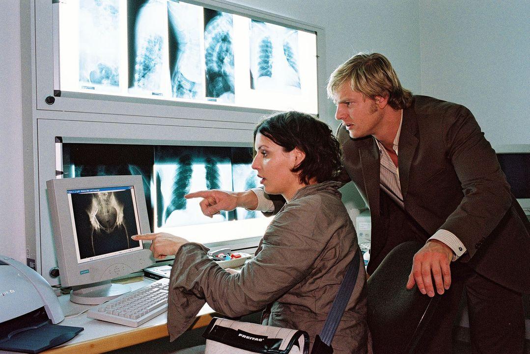 Nina (Elena Uhlig, l.) und Leo (Henning Baum, r.) analysieren die Röntgenaufnahmen der Toten. - Bildquelle: Christian A. Rieger Sat.1