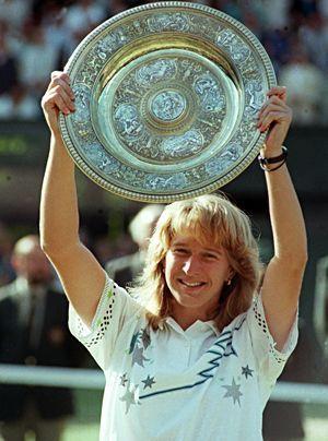 Nach ihrem ersten Sieg bei den All England Championships in Wimbledon präsentiert Steffi Graf am 2.7.1988 die Silberschale den Fotografen. Die Br - Bildquelle: dpa