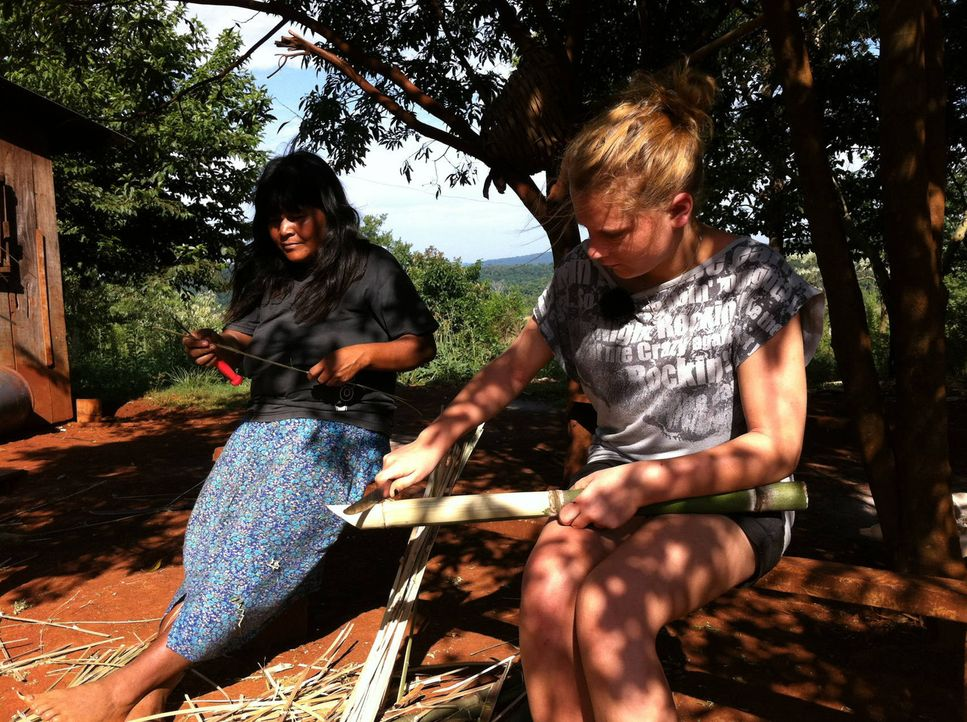 Gastmutter Carolina (l.) erklärt Sina (r.), wie man Bambus bearbeitet ... - Bildquelle: kabel eins