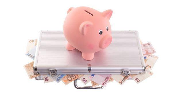 Sparschwein auf Metallkoffer gefüllt mit Euroscheinen