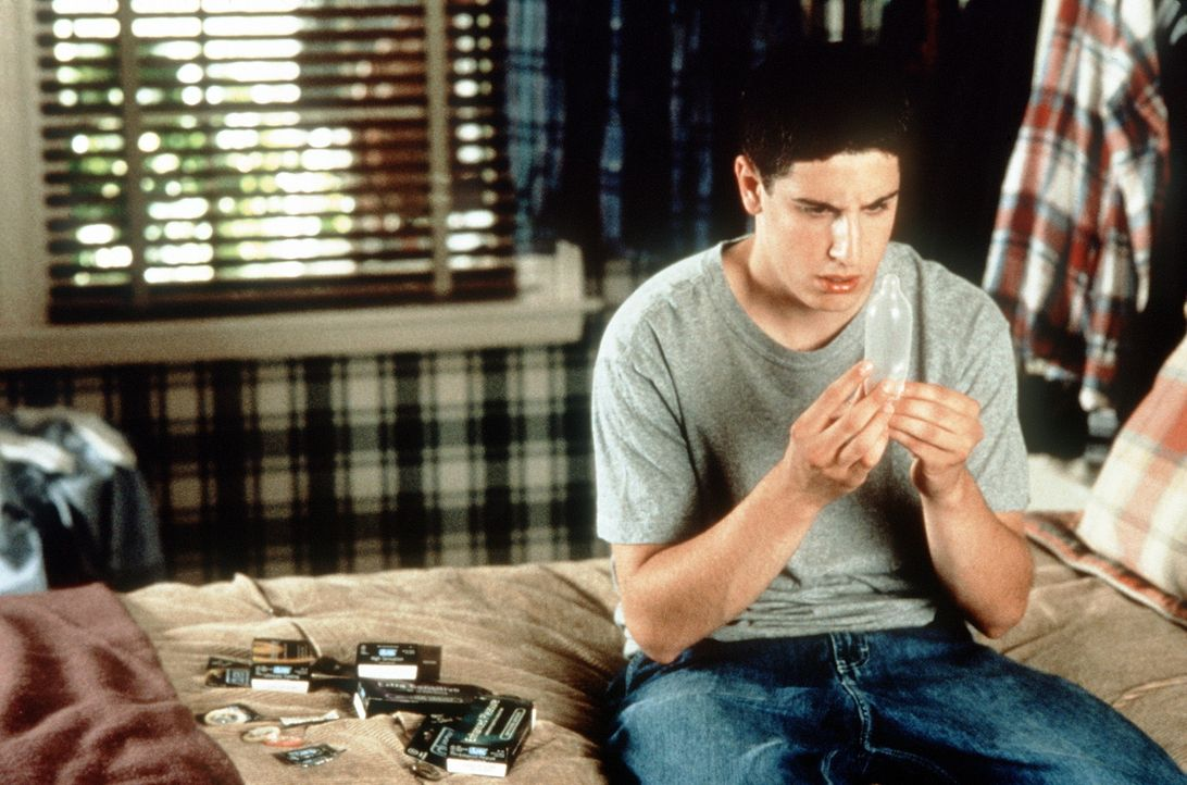 Um auf alles vorbereitet zu sein, setzt sich der unerfahrene Jim (Jason Biggs) mit einem Kondom und dessen Funktion auseinander. Doch da ist niemand... - Bildquelle: Constantin Film