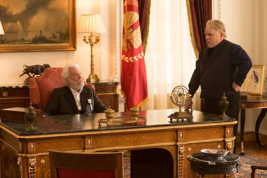 Präsident Snow (Donald Sutherland, l.) glaubt, in Plutarch Heavensbee (Philip Seymore Hoffman, r.) den besten Spielmacher gefunden zu haben, bis die... - Bildquelle: Studiocanal GmbH