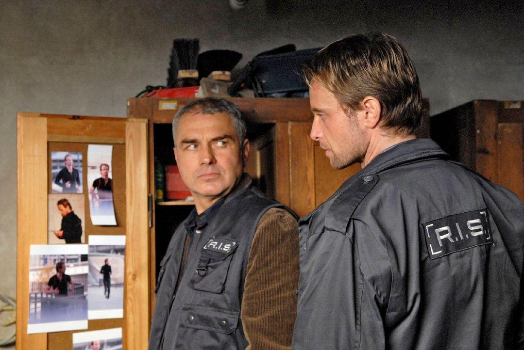Paul (Hansa Czypionka, l.) findet in den Kellerräumen von Doeblin Fotos, die Philip (Julian Weigend, r.) beim Joggen im Park zeigen. - Bildquelle: Christoph Assmann Sat.1