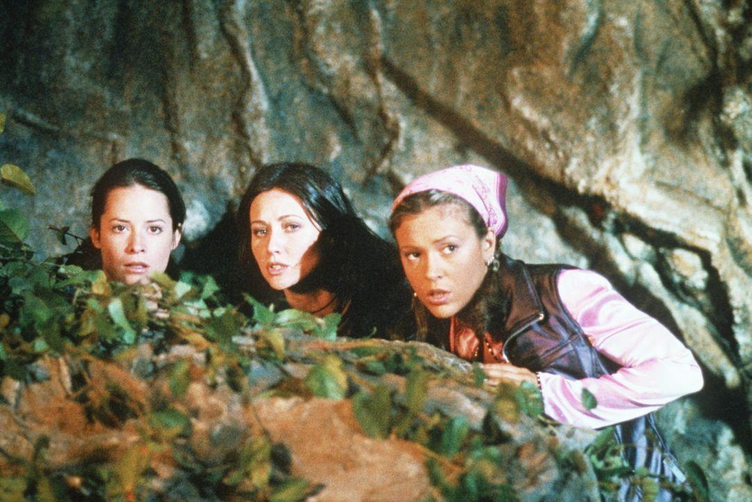 Hinter einem Felsen beobachten Piper (Holly Marie Combs, l.), Prue (Shannen Doherty, M.) und Phoebe (Alyssa Milano, r.) das Geschehen ... - Bildquelle: Paramount Pictures