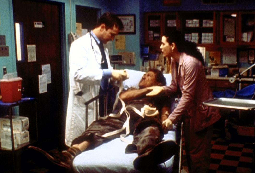 Carter (Noah Wyle, l.) stellt auf brutale Weise einen Obdachlosen ruhig. Hathaway (Julianna Margulies, r.) ist schockiert. - Bildquelle: TM+  2000 WARNER BROS.