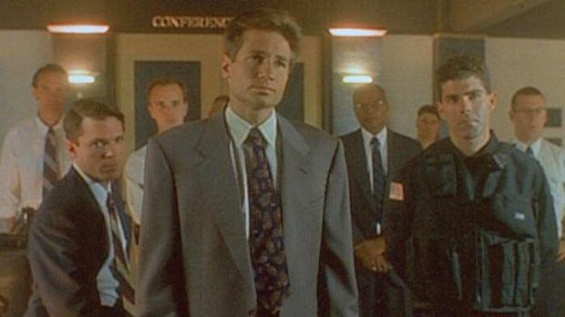 Mulder (David Duchovny, vorne) und ein ganzes Team von FBI-Leuten verhandeln...