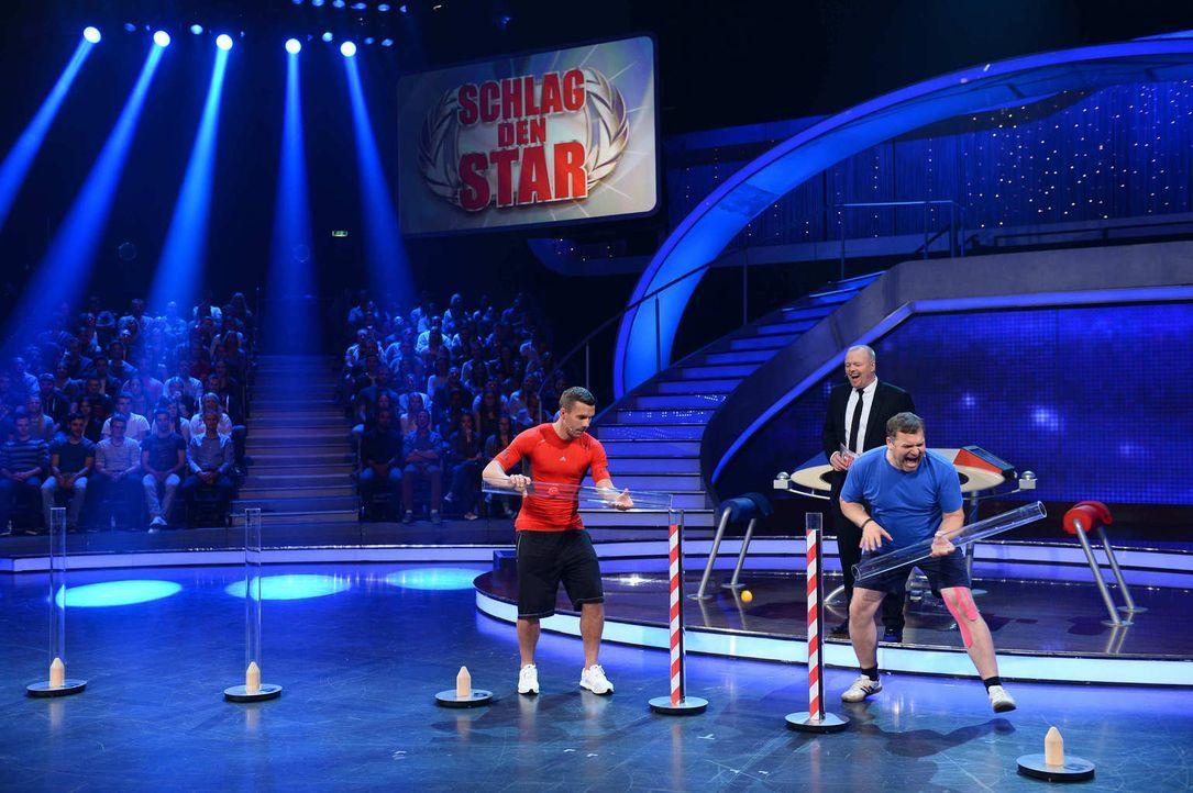 Gastgeber Stefan Raab (M.) lässt Lukas Podolski (l.) und Elton (r.) gegeneinander antreten ... - Bildquelle: Willi Weber ProSieben
