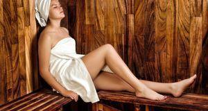 Frau mit Handtuch beim Sauna-Besuch