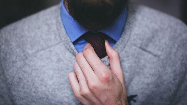Griff an die Krawatte ist ein Signal der Körpersprache