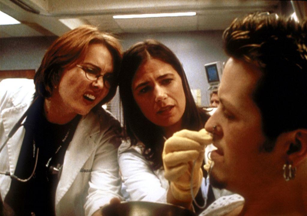 (v.l.n.r.) Weaver (Laura Innes) und Abby (Maura Tierney) verarzten Tom (Casey Lewis), der ein Problem mit seinem Nasenring hat. - Bildquelle: TM+  2000 WARNER BROS.