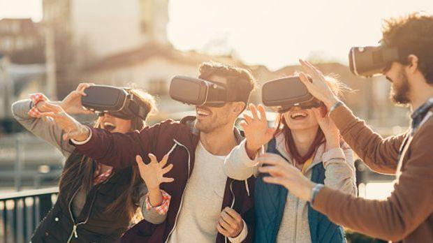 Freunde tragen im Freien VR-Brillen und freuen sich über die ungewohnte Persp...