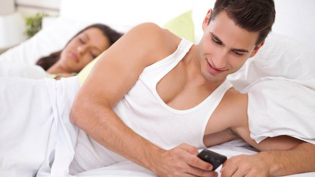 Untreuer Mann schreibt im Bett Nachrichten an seine Geliebte, während seine F...