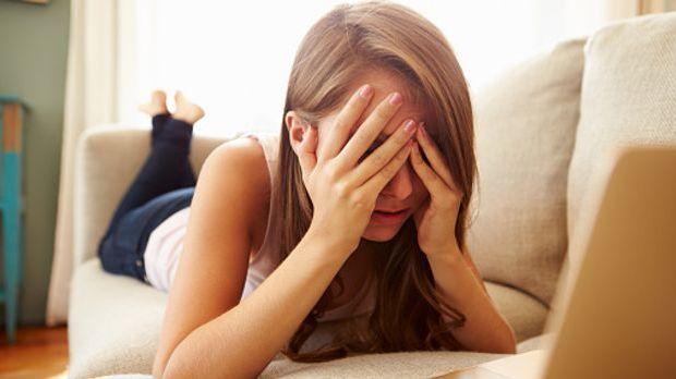 Frau liegt auf dem Bauch und hält sich die Hände vors Gesicht